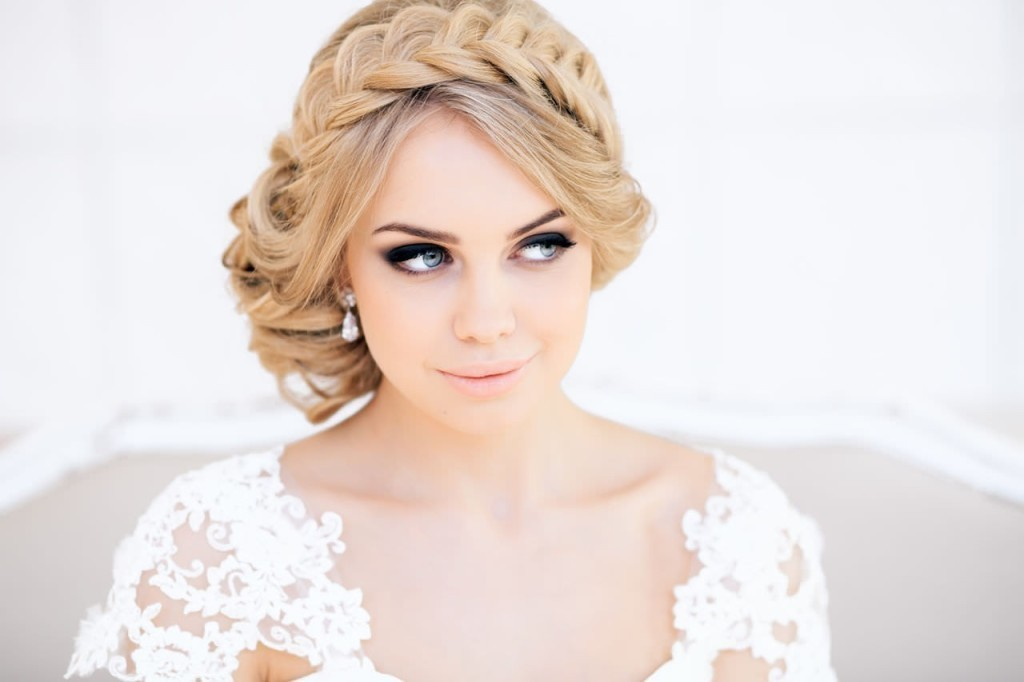 A blond bride with the braid looks to the side