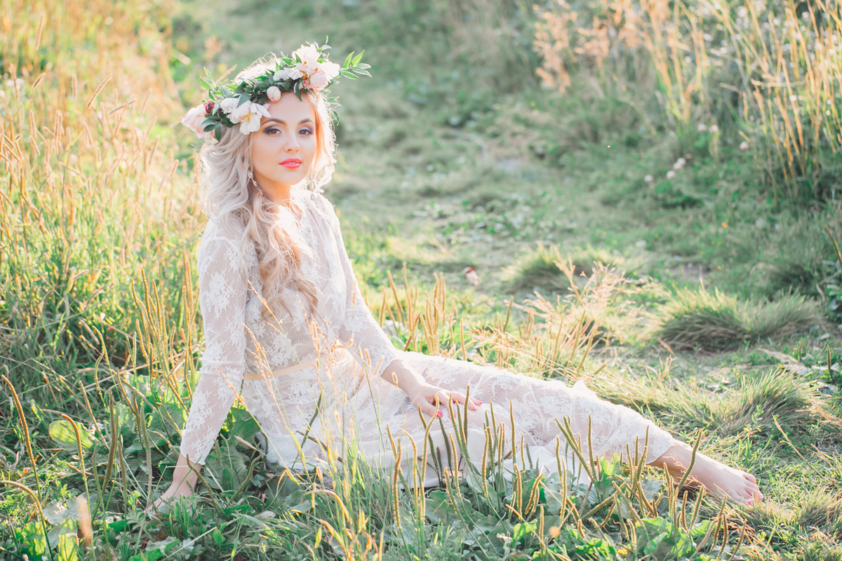 Bride with the flowers in her hair sits on the ground of the field