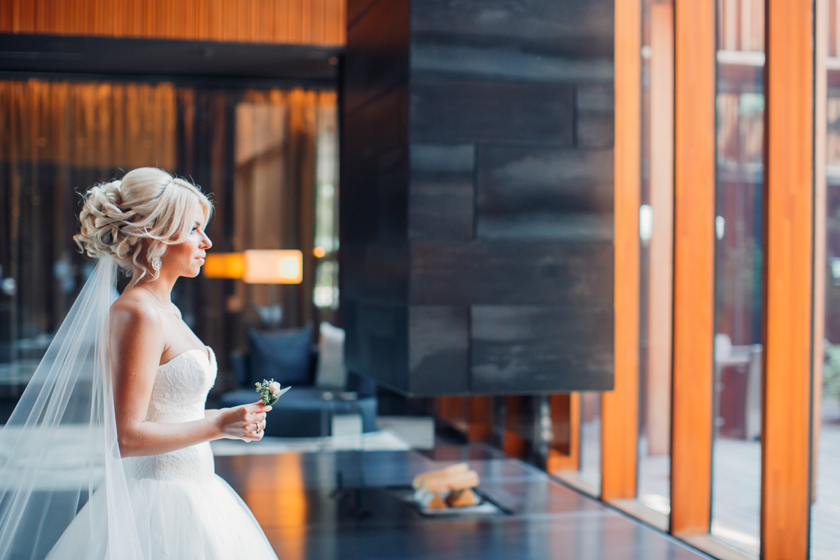 A blond bride standing in the room and looking out of the window